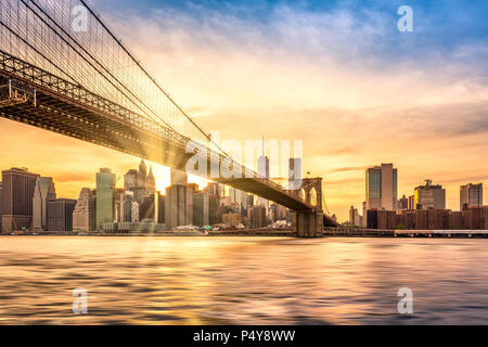 Brooklyn Bridge at sunset viewed from Brooklyn Bridge park, in New York City - Stock Photo