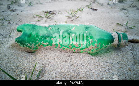 Empty single use plastic bottle washed up on beach - Stock Photo