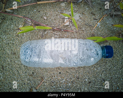 Empty single use plastic bottle washed up on beach - Stock Photo
