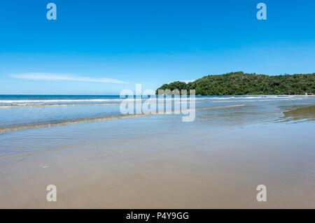 Waves from the South China Sea break on to the beach in Kota Kinabalu, Borneo, Malaysia - Stock Photo