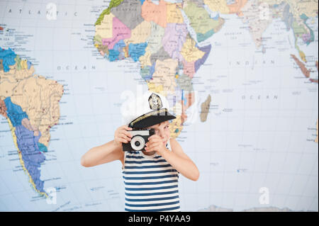 funny little boy in captain hat taking picture by old retro film camera near world map - Stock Photo