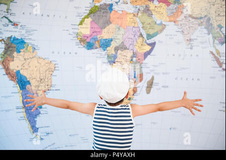 little child in captain hat spreading hands to world map - Stock Photo