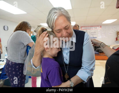 Sister Norma Pimentel hugs a volunteer as immigrant families released by U.S. Immigration and Customs Enforcement (ICE) take respite at a Catholic Charities shelter in McAllen TX while awaiting disposition of their deportation cases. - Stock Photo