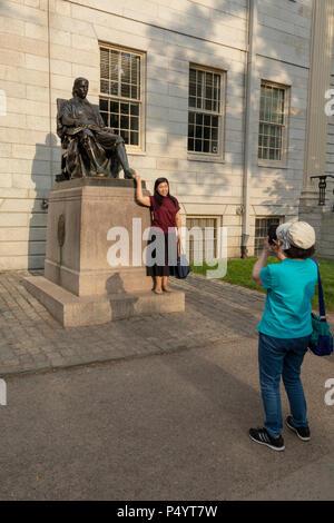 tourist being photographed rubbing toe of bronze statue of John Harvard by Daniel Chester French in Harvard Yard, Cambridge, Massachusetts, USA - Stock Photo