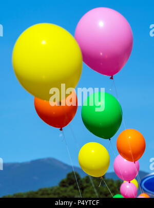 Colorful balloons; windy day; automobile dealership; Salida; Colorado; USA - Stock Photo