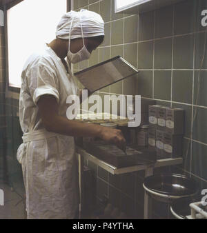 Riyadh, 1960s, female assistant in uniform in the operating theatre at the National hospital, Saudi Arabia. In 1951 the Ministry of Heath was established and health care expanded and new hospitals were built. - Stock Photo