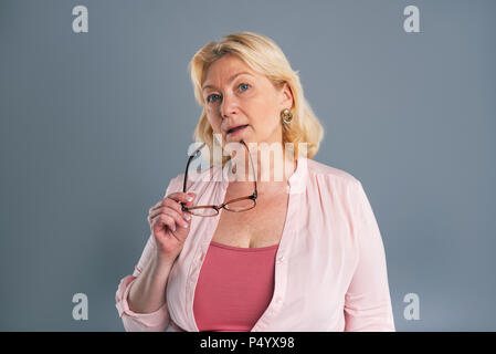 Charming senior woman posing while holding glasses - Stock Photo