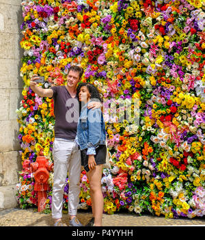 Young white man and beautiful black woman taking selfies before the colorful flowery wall - Stock Photo