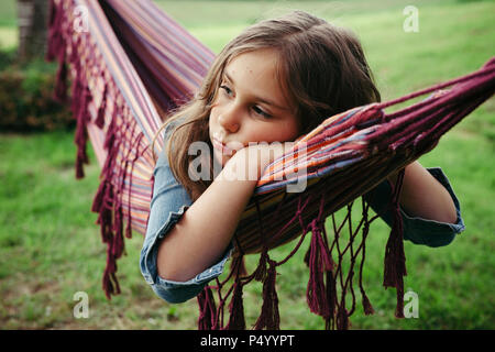 Portrait of sad girl lying in hammock - Stock Photo