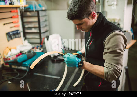 Man in workshop cutting wood with scissors - Stock Photo