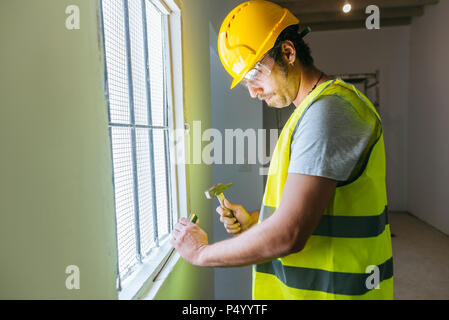 Worker with hammer working at the window - Stock Photo