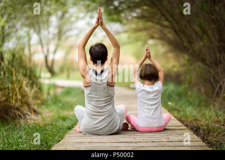 Rear view of mother and daughter doing yoga on boardwalk - Stock Photo