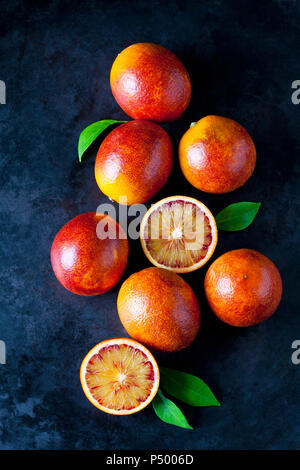 Whole and sliced blood oranges on dark ground - Stock Photo