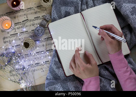 Hands of woman writing in notebook