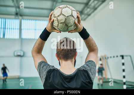Close-up of indoor soccer player throwing in the ball - Stock Photo