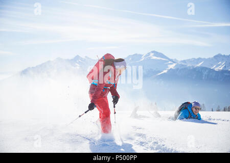 Austria, Tyrol, snowshoe hikers running through snow, man falling - Stock Photo