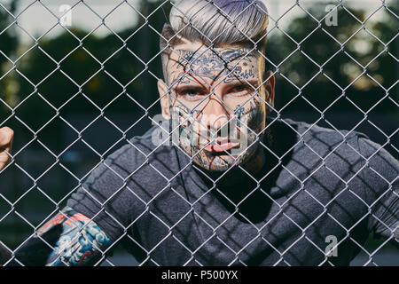 Portrait of tattooed young man behind fence - Stock Photo