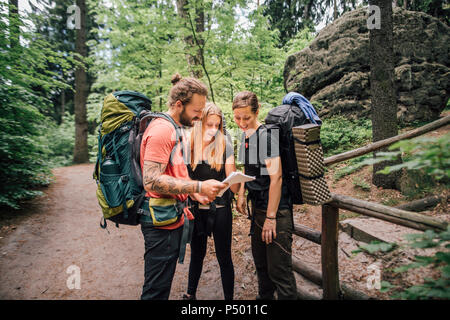 Friends on a hiking trip reading map - Stock Photo