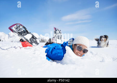 Austria, Tyrol, snowshoe hiker and dog, having fun in the snow - Stock Photo