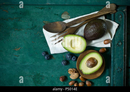 Cloth, salad cutlery, avocados, blueberries and nuts on green ground - Stock Photo