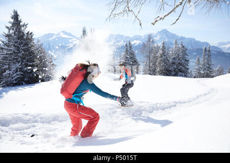 Austria, Tyrol, couple having fun in the snow - Stock Photo