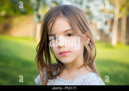 Portrait of little girl in the garden - Stock Photo