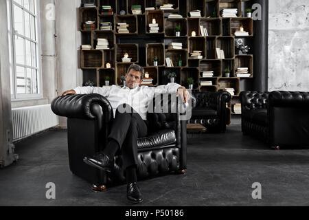 Portrait of mature man sitting in black armchair in loft - Stock Photo