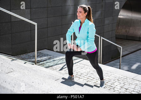 Young woman doing stretching exercise on stairs in the city - Stock Photo