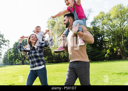 Happy parents carrying children on shoulders in a park - Stock Photo