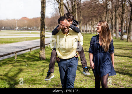 Happy family walking in a park - Stock Photo