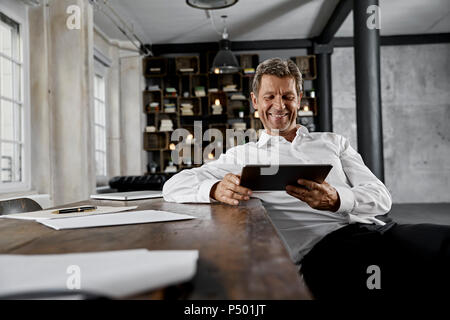 Smiling mature man using digital tablet in loft office - Stock Photo