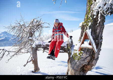 Austria, Tyrol, female hiker sitting on branch - Stock Photo