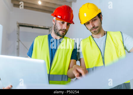 Workers working with laptop and plane on the construction site - Stock Photo