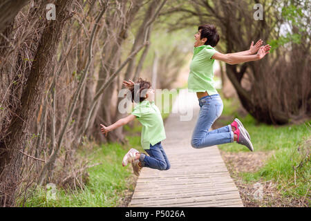 Happy mother and daughter jumping on boardwalk - Stock Photo