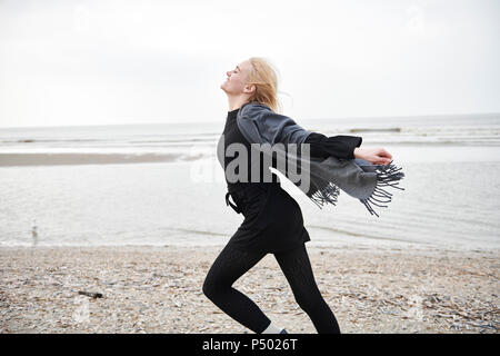 Netherlands, happy blond young woman running on the beach - Stock Photo