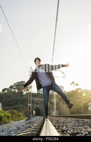 Young man standing on railroad track - Stock Photo
