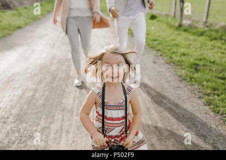 Portrait of excited little girl with camera - Stock Photo