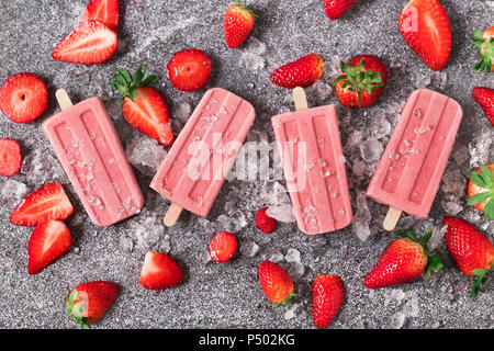 Four homemade strawberry ice lollies, ice and strawberries on marble - Stock Photo
