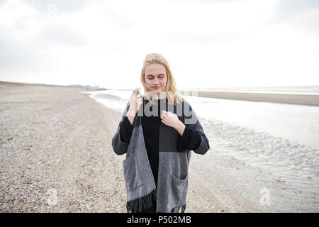 Netherlands, blond young woman wearing gray jacket on the beach - Stock Photo