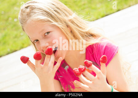 Portrait of smiling girl with raspberries on  fingers - Stock Photo