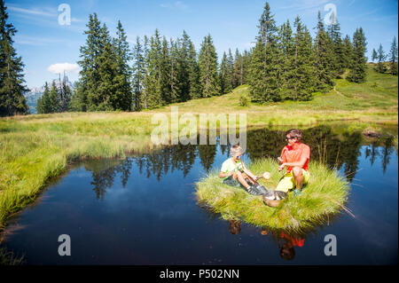 Austria, Salzburg State, Untertauern, father and son grilling on small island - Stock Photo