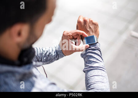 Close-up of athlete checking smartwatch - Stock Photo