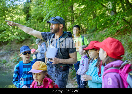 Man talking to kids on a field trip in forest - Stock Photo
