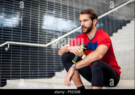 Man sitting on stairs having a break from running - Stock Photo