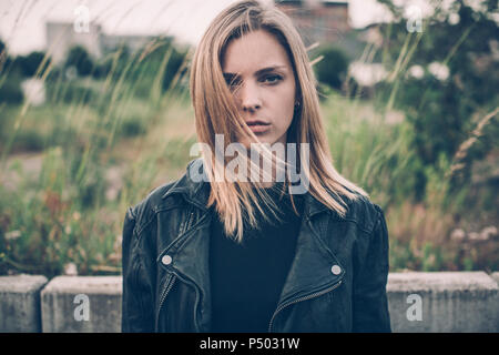 Portrait of serious young woman dressed in black - Stock Photo