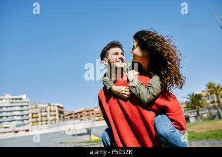 Happy young man giving girlfriend a piggyback ride - Stock Photo