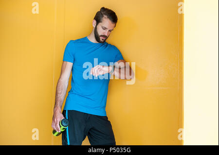 Man having a break from running checking the time - Stock Photo