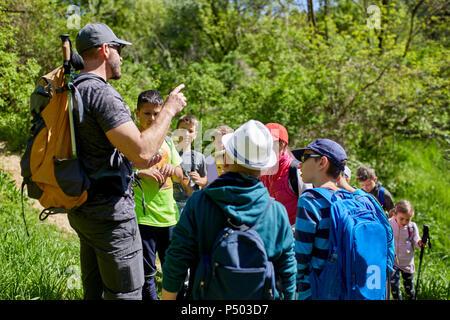 Man talking to kids on a field trip on trail - Stock Photo