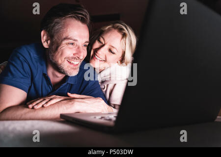 Happy couple lying on couch at home using laptop - Stock Photo