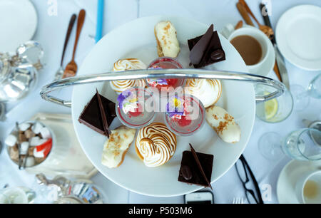 looking down onto a table with a English afternoon tea on it, a round plate of colourful cakes with silver tea and coffee pots and white cups white li - Stock Photo